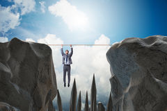 The businessman hanging on rope in danger concept Stock Photos