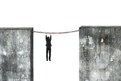 Businessman hanging rusty chain connected concrete walls Stock Photo