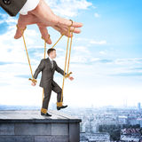 Businessman hanging on strings like marionette Stock Photos