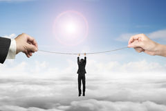 Businessman hanging on tightrope with man and woman hands holdin Royalty Free Stock Photos
