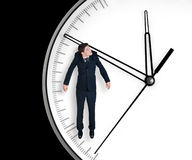 Businessman hangs on an arrow of clock. Isolated on black background Stock Photo