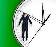 Businessman hangs on an arrow of clock. Isolated on black background Stock Photography