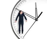 Businessman hangs on an arrow of clock Stock Image