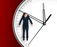 Businessman hangs on an arrow of clock Stock Photography