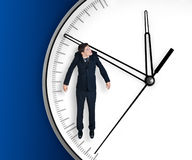 Businessman hangs on an arrow of clock Stock Photos