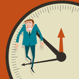 Businessman hangs on an arrow of clock. Royalty Free Stock Photography