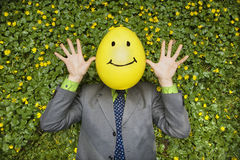 Businessman with Happy Balloon Face. Businessman lies in a flower bed with a yellow balloon happy face on his head. Horizontal shot stock photo