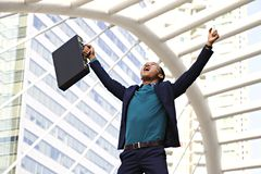 Businessman is happy in the city. Businessman is lifting brief case yelling happily in the city Stock Image