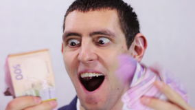 Businessman is Happy his Money. Businessman counts tens of thousands of Hryvnia (Ukrainian currency), holding them in their hands.  A man dressed in a business stock video footage