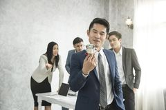 Businessman happy pride with win cup and business team jealous. Behind royalty free stock photo