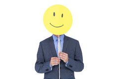 Businessman with happy smiley faced balloon. Portrait of a young businessman holding happy smiley faced balloon on white background Royalty Free Stock Image