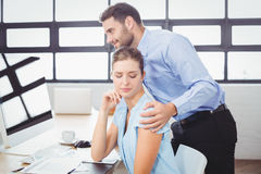 Businessman harassing female colleague at computer desk stock images