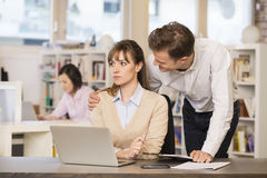 Businessman harassing his colleague at work Royalty Free Stock Photos