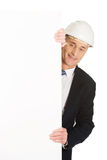 Businessman with hard hat holding empty banner Stock Photo