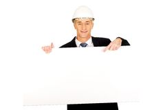 Businessman with hard hat holding empty banner Stock Photos
