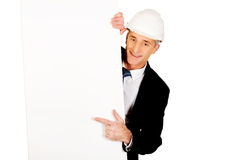 Businessman with hard hat holding empty banner Stock Images
