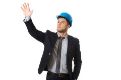 Businessman in hard hat showing copyspace. Royalty Free Stock Photography