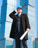 Businessman in hard hat talking on cell phone. And holding drawing in his hand,on skyscrapers background Stock Photo