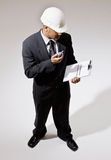 Businessman in hard-hat with walkie-talkie Stock Photography