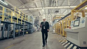 Businessman in hard hat walking through factory stock video footage