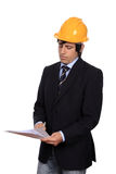 Businessman with hardhat reading Royalty Free Stock Image
