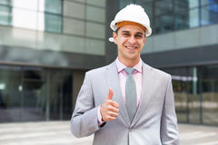 Businessman in hardhat showing thumbs up stock photos