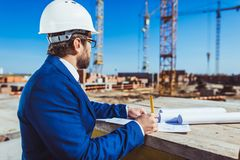 Businessman in hardhat and suit working with building plans. At construction site royalty free stock photo
