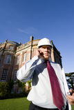 Businessman in hardhat using mobile phone by manor house, low angle view Royalty Free Stock Photo