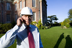 Businessman in hardhat using mobile phone by manor house, portrait Stock Photo