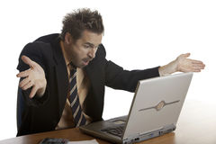 Businessman has computer problem. Businessman sitting on his desk and is quite angry on his laptop because of a computer crash Stock Image