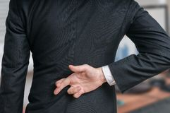 Businessman has crossed fingers behind his back. Good luck or dishonesty concept.  Stock Image