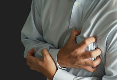 Businessman has Heart Attack. On dark background Stock Photography