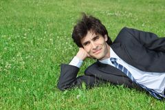 Businessman has rest, lying on grass Royalty Free Stock Image