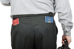 Businessman has Russian and Israeli passports in rear pockets. Businessperson has Russian and Israeli passports in rear pockets his black trousers. View from the Royalty Free Stock Image
