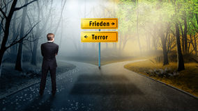 Businessman has to decide which direction is better with the words `Peace` and `Terror` on the road. In German stock photos