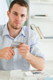Businessman has to get rid of his credit card. Young businessman has to get rid of his credit card Stock Photography
