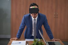 Businessman has virtual presentation. Young manager wearing virtual reality goggles standing near the table and has virtual business presentation at office stock image