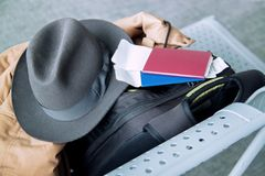 Businessman in a hat standing at the airport,talking by cellphone .Set of traveler, top view. Hat, passport, ticket, backpack stock images