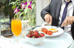 Businessman have a healthy breakfast. Businessman having a breakfast with frie egg, orange juice and coffee Stock Photography