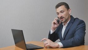 Businessman have a heavy conversation. Businessman is finishing a heavy conversation on the phone. The man shakes his head in displeasure and sighs. A person Stock Photos