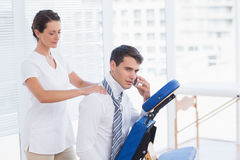 Businessman having back massage while talking on the phone. In medical office Stock Image