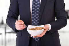 Businessman having breakfast with cereal bowl. Stock Images