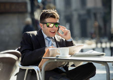Businessman  having breakfast coffee reading newspaper news talking on mobile phone Royalty Free Stock Photo