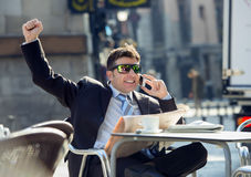 Businessman having breakfast coffee reading newspaper talking happy on mobile phone doing victory sign. Young happy businessman sitting outdoors on street bar Stock Image