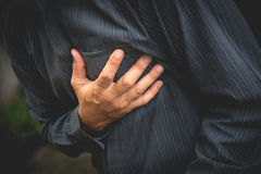 Businessman having chest pain and heart attack. Royalty Free Stock Image