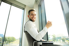 Businessman having a coffee break and relaxing at window Stock Photo
