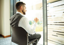 Businessman having a coffee break and relaxing at window Stock Photography