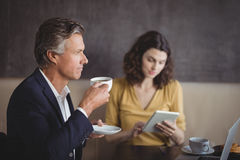Businessman having coffee while colleague using digital tablet Stock Photos