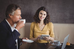 Businessman having coffee while colleague using digital tablet Stock Photography
