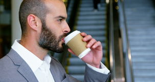 Businessman having coffee from disposable cup stock video footage